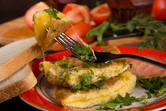 Omelet with cheese and fresh herbs on the table Royalty Free Stock Image
