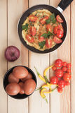 Omelet with cherry tomato. And cayenne pepper in frying pan Royalty Free Stock Images