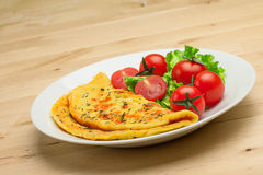 Omelet with cherry tomatoes and green salad with herbs Stock Image