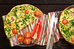 Omelet with cherry tomatoes, sweet pepper and herbs for 2 persons. Royalty Free Stock Images