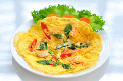 Omelet with cooked seafood and greens. On a white background royalty free stock photo