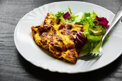 Omelet with fresh mixed salad leaves in a plate. On dark wooden background Stock Photography