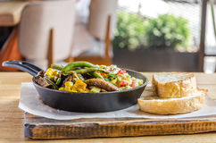 Omelet in a frying pan with vegetables, bread and cutlery on a wooden table, side view stock photography