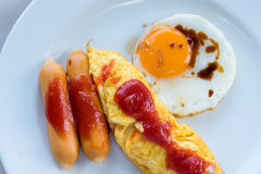 Omelet, grilled sausages, tomato on a white plate. Stock Images