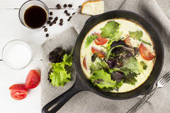 Omelet with lettuce and tomatoes, coffee and milk on a white woo. Den background. Top view Royalty Free Stock Images