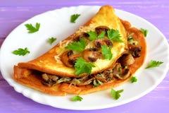 Omelet met gebraden paddestoelen, kaas en verse peterselie Stock Fotografie