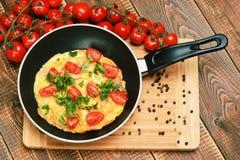 Omelet met ham, tomaten en chees op de pan Stock Afbeeldingen