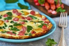 Omelet met spinazie, kaas en Beierse worsten Stock Afbeeldingen
