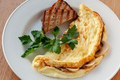 Omelet with mushrooms, decorated with herbs and toast royalty free stock photo