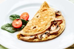Omelet with mushrooms served on white plate with cherry tomatoes and spinach.  royalty free stock photos