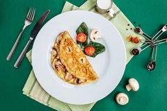Omelet with mushrooms served on white plate with cherry tomatoes and spinach.  royalty free stock photo