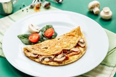 Omelet with mushrooms served on white plate with cherry tomatoes and spinach.  stock images