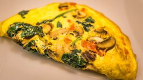 Vegetable omelet closeup. Omelet of mushrooms, tomatoes and spinach stock photo