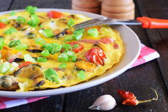 Omelet with mussels, cherry tomatoes and green onions on a ceramic plate on a black background. Royalty Free Stock Photo