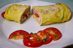 Omelet, omelette, frittata. Omelet with ham and cheese. Garnish with tomatoes and capers Stock Photography