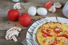 Omelet with onion, tomatoes and mushrooms. In beautiful white plates. Natural homemade food concept Royalty Free Stock Image