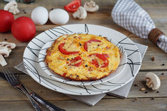 Omelet with onion, tomatoes and mushrooms. In beautiful white plates. Natural homemade food concept Stock Image
