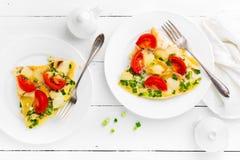 omelet Os ovos fritaram Ovos mexidos com cebola verde e o tomate fresco Omlette na placa branca Opinião superior do café da manhã foto de stock royalty free