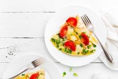 omelet Os ovos fritaram Ovos mexidos com cebola verde e o tomate fresco Omlette na placa branca Opinião superior do café da manhã foto de stock