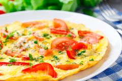 Omelet with paprika, tomato and herbs stock image