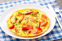 Omelet with paprika, tomato and herbs Stock Photo