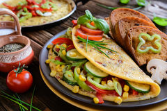 Omelet with pepper, tomato, corn, green onion, cucumber, mushrooms and fried bread. On a wooden background Royalty Free Stock Photography