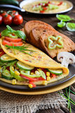 Omelet with pepper, tomato, corn, green onion, cucumber, mushrooms and fried bread Royalty Free Stock Image