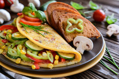 Omelet with pepper, tomato, corn, green onion, cucumber, mushrooms and fried bread Stock Photography