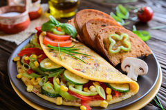 Omelet with pepper, tomato, corn, green onion, cucumber, mushrooms and fried bread Stock Photos
