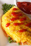 Omelet with rice, green peas and ketchup macro. vertical Royalty Free Stock Images