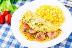 Omelet with sausage, tomato and herbs Royalty Free Stock Images