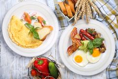 Omelet and scrambled eggs with salmon, bacon royalty free stock image