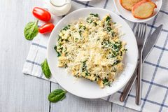 Omelet with spinach. And cheese on a white plate, coffee and orange juice on a white wooden table. Serving for breakfast royalty free stock photography