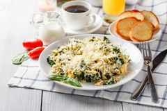 Omelet with spinach. And cheese on a white plate, coffee and orange juice on a white wooden table. Serving for breakfast stock photos