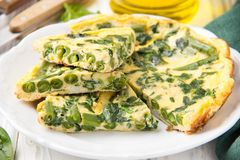 Omelet with spinach and green beans, healthy food. Egg and milk Frittata, delicious Breakfast on white wooden background. Omelet with spinach and green beans stock images