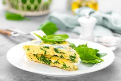 Omelet with spinach leaves. Omelette on plate, scrambled eggs. On plate. Breakfast royalty free stock image