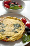 Omelet with spinach olives and cherry tomatoes. Omelet with green spinach olives and red cherry tomatoes on white plate Stock Image