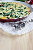 Omelet with spinach. In a pan placed on a table nearby lies two forks Royalty Free Stock Image