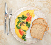 Omelet with spinach, tomatoes and mushrooms on round plate. Top view royalty free stock photos
