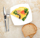 Omelet with spinach, tomatoes and mushrooms on round plate Stock Photography