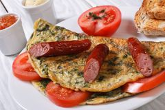 Omelet with spinach, tomatoes and sausage Royalty Free Stock Images