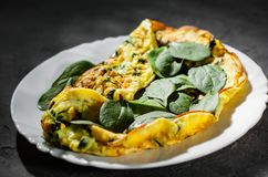 Omelet with spinach in white plate on Dark. Grey black slate background stock photography
