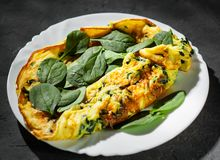 Omelet with spinach in white plate on Dark. Grey black slate background stock photo