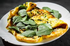 Omelet with spinach in white plate on Dark. Grey black slate background stock image