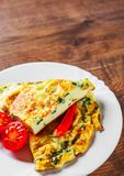 Omelet with spinach in white plate on wooden table. Background stock photos
