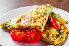 Omelet with spinach in white plate on wooden table. Background royalty free stock images