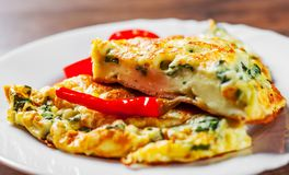 Omelet with spinach in white plate on wooden table. Background stock photography