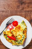 Omelet with spinach in white plate on wooden table. Background stock photo