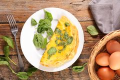 Omelet and spinach. On wood royalty free stock photos