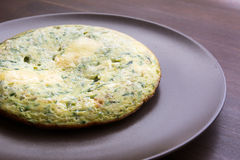 Omelet with spinach and zucchini with melted cheese on brown plate stock image